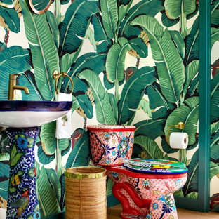 Inspiration for a tropical powder room in Los Angeles with a two-piece toilet, multi-coloured walls, light hardwood floors and a pedestal sink.