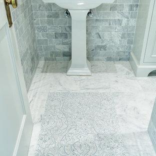 Idée de décoration pour un WC et toilettes tradition de taille moyenne avec un placard avec porte à panneau encastré, des portes de placard blanches, un carrelage gris, du carrelage en marbre, un mur gris, un sol en marbre, un lavabo de ferme, un plan de toilette en bois et un sol blanc.