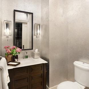 Modelo de aseo tradicional, pequeño, con lavabo bajoencimera, armarios con paneles con relieve, puertas de armario marrones, encimera de mármol, sanitario de dos piezas, baldosas y/o azulejos beige, paredes grises y suelo de piedra caliza