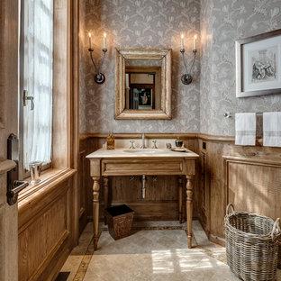 Новые идеи обустройства дома: туалет в классическом стиле с фасадами цвета дерева среднего тона, полом из известняка, врезной раковиной, серыми стенами и бежевым полом