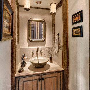 Неиссякаемый источник вдохновения для домашнего уюта: туалет в классическом стиле с фасадами с утопленной филенкой, керамогранитной плиткой, бежевыми стенами, паркетным полом среднего тона, настольной раковиной, столешницей из гранита и искусственно-состаренными фасадами