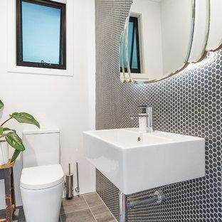 Пример оригинального дизайна: туалет в современном стиле с белыми фасадами, раздельным унитазом, черно-белой плиткой, керамогранитной плиткой, черными стенами, полом из керамогранита, раковиной с несколькими смесителями, столешницей из искусственного камня, серым полом и белой столешницей