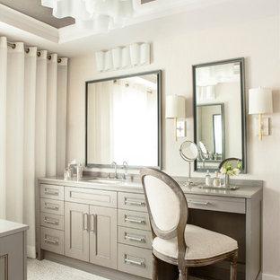 Cette photo montre un WC et toilettes tendance de taille moyenne avec un mur beige, un placard avec porte à panneau encastré, des portes de placard beiges et un plan de toilette gris.