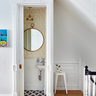 Exemple d'un petit WC et toilettes chic avec un mur beige, un lavabo suspendu, un sol multicolore et un sol en carreaux de ciment.