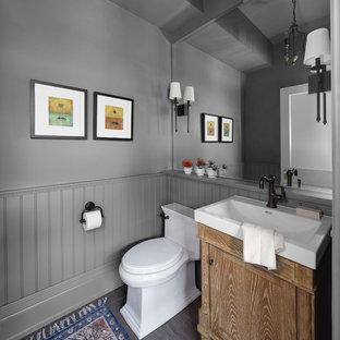 Idées déco pour un petit WC et toilettes avec un placard avec porte à panneau encastré, des portes de placard en bois clair, un mur gris, un sol en carrelage de porcelaine, un lavabo intégré, un sol gris et un plan de toilette blanc.