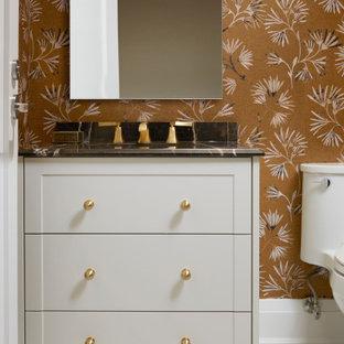На фото: туалет среднего размера в стиле современная классика с фасадами с утопленной филенкой, серыми фасадами, разноцветными стенами, полом из терраццо, врезной раковиной, бежевым полом, черной столешницей, встроенной тумбой и обоями на стенах