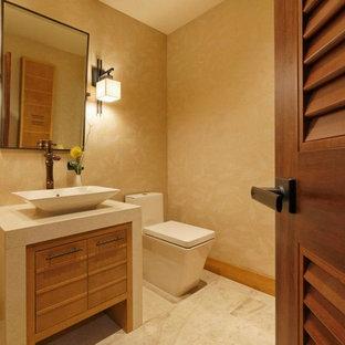 На фото: туалет среднего размера в современном стиле с плоскими фасадами, светлыми деревянными фасадами, унитазом-моноблоком, бежевыми стенами, полом из травертина, настольной раковиной, столешницей из известняка и бежевым полом с
