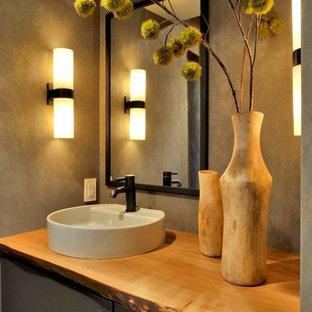 Cette photo montre un petit WC et toilettes tendance avec un placard à porte plane, des portes de placard grises, un WC à poser, un mur gris, un lavabo de ferme, un plan de toilette en bois et un plan de toilette marron.
