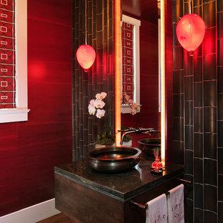 Bild på ett orientaliskt toalett, med skåp i mörkt trä, röda väggar, mellanmörkt trägolv och ett fristående handfat