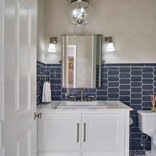 Пример оригинального дизайна: туалет среднего размера в современном стиле с фасадами островного типа, белыми фасадами, унитазом-моноблоком, бежевыми стенами, полом из керамической плитки, накладной раковиной, столешницей из кварцита, разноцветным полом и белой столешницей