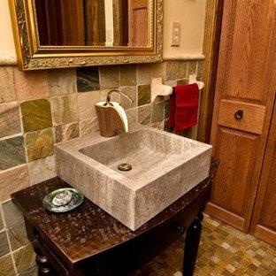 Idées déco pour un grand WC et toilettes contemporain avec des portes de placard en bois sombre, un carrelage beige, un carrelage marron, du carrelage en travertin, un mur beige, un sol en travertin, une vasque, un plan de toilette en bois et un sol marron.
