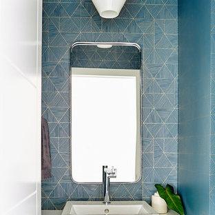 Idee per un bagno di servizio contemporaneo con top in quarzo composito, pareti blu, lavabo a bacinella e top bianco
