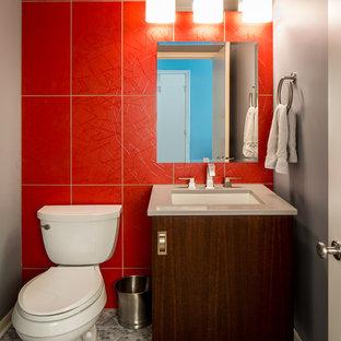 Пример оригинального дизайна: туалет среднего размера в современном стиле с врезной раковиной, плоскими фасадами, темными деревянными фасадами, столешницей из искусственного камня, раздельным унитазом, красной плиткой, керамогранитной плиткой, красными стенами и серой столешницей