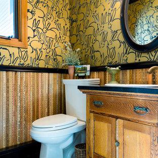 Ejemplo de aseo ecléctico, pequeño, con armarios tipo mueble, puertas de armario de madera oscura, sanitario de dos piezas, paredes multicolor, suelo de linóleo, lavabo encastrado, encimera de granito y suelo multicolor
