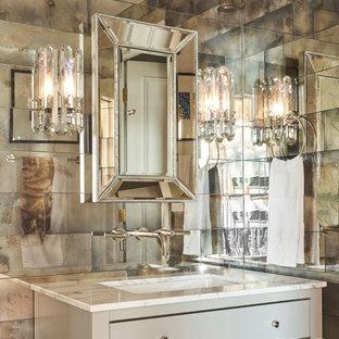 Idee per un bagno di servizio tradizionale di medie dimensioni con consolle stile comò, ante grigie, piastrelle a specchio, lavabo sottopiano, top in marmo e top bianco