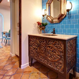 Стильный дизайн: маленький туалет в средиземноморском стиле с врезной раковиной, фасадами островного типа, темными деревянными фасадами, синей плиткой, керамической плиткой, полом из терракотовой плитки и синими стенами - последний тренд