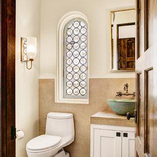 ダラスの小さい地中海スタイルのおしゃれなトイレ・洗面所 (ベッセル式洗面器、インセット扉のキャビネット、白いキャビネット、ライムストーンの洗面台、一体型トイレ、ベージュのタイル、白い壁、無垢フローリング、ライムストーンタイル) の写真