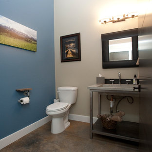 Exemple d'un grand WC et toilettes industriel avec des portes de placard en bois brun, un WC à poser, un carrelage gris, un mur gris, béton au sol, un lavabo intégré et un plan de toilette en verre recyclé.