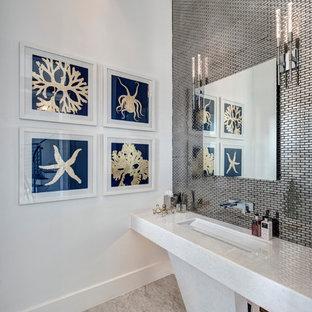 Cette photo montre un WC et toilettes bord de mer avec carrelage en métal, un mur blanc, un lavabo encastré, un sol gris et un plan de toilette blanc.