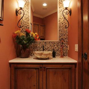 Пример оригинального дизайна: туалет среднего размера в средиземноморском стиле с фасадами с выступающей филенкой, темными деревянными фасадами, унитазом-моноблоком, бежевой плиткой, плиткой из листового камня, оранжевыми стенами, полом из керамической плитки, раковиной с пьедесталом и столешницей из талькохлорита