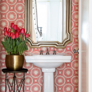 Example of a mid-sized transitional dark wood floor powder room design in New York with a pedestal sink and red walls