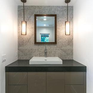 Aménagement d'un WC et toilettes moderne de taille moyenne avec un lavabo posé, des portes de placard marrons, un plan de toilette en quartz modifié, un mur blanc, un sol en carrelage de céramique, un carrelage gris et un plan de toilette noir.