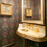 Example of a classic dark wood floor powder room design in DC Metro with an undermount sink, green cabinets, onyx countertops and multicolored walls