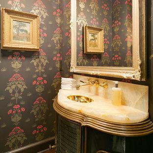 Inspiration pour un WC et toilettes traditionnel avec un lavabo encastré, des portes de placards vertess, un plan de toilette en onyx, un mur multicolore et un sol en bois foncé.