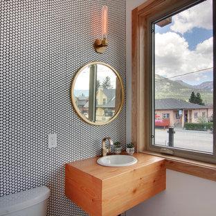 Cette photo montre un WC et toilettes tendance de taille moyenne avec un carrelage noir et blanc, un mur gris, un lavabo posé, des portes de placard en bois brun, un plan de toilette en bois et un plan de toilette marron.