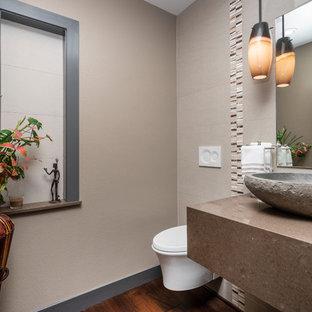 Réalisation d'un petit WC et toilettes design avec un WC suspendu, un carrelage beige, des carreaux de porcelaine, un mur beige, un sol en bois foncé, une vasque, un plan de toilette en quartz modifié, un sol marron et un plan de toilette marron.