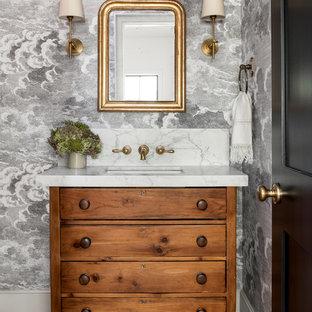 Ejemplo de aseo campestre con armarios tipo mueble, puertas de armario de madera oscura, paredes grises, suelo de madera oscura, lavabo bajoencimera, suelo marrón y encimeras grises