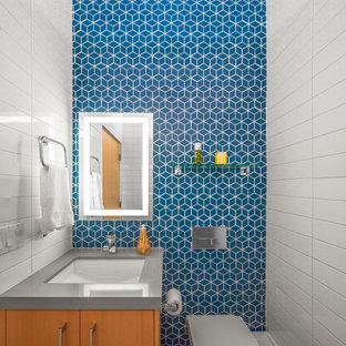 Idéer för att renovera ett 50 tals grå grått badrum, med keramikplattor, släta luckor, skåp i mellenmörkt trä, en vägghängd toalettstol, vit kakel, blå kakel, blå väggar och ett undermonterad handfat