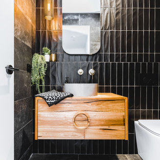 Small contemporary powder room in Sydney with black tile, flat-panel cabinets, medium wood cabinets, a one-piece toilet, a vessel sink, wood benchtops, grey floor, brown benchtops and a floating vanity.
