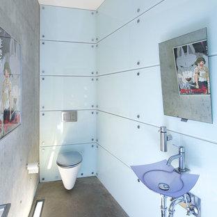 Стильный дизайн: маленький туалет в современном стиле с подвесной раковиной и бетонным полом - последний тренд