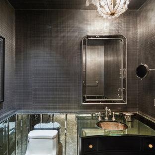 Réalisation d'un WC et toilettes tradition avec un mur gris, un placard en trompe-l'oeil, des portes de placard noires, un carrelage gris, des carreaux de miroir, un lavabo encastré et un plan de toilette en verre.