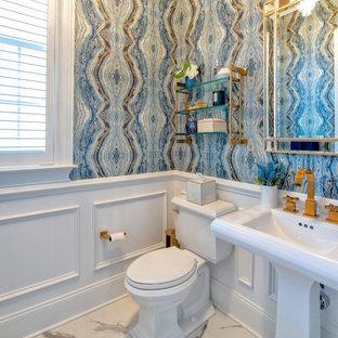 Cette photo montre un grand WC et toilettes tendance avec des portes de placard blanches, un WC séparé, un mur multicolore, un sol en marbre, un lavabo de ferme, un sol blanc, meuble-lavabo sur pied et du papier peint.