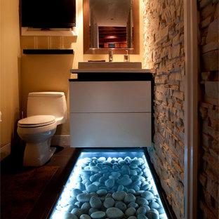 Kleine Moderne Gästetoilette mit flächenbündigen Schrankfronten, weißen Schränken, gelber Wandfarbe, dunklem Holzboden, Mineralwerkstoff-Waschtisch, Toilette mit Aufsatzspülkasten und Aufsatzwaschbecken in New York