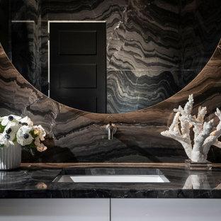 Стильный дизайн: большой туалет в стиле модернизм с плоскими фасадами, белыми фасадами, биде, черной плиткой, мраморной плиткой, черными стенами, мраморным полом, врезной раковиной, мраморной столешницей, черным полом, черной столешницей и подвесной тумбой - последний тренд