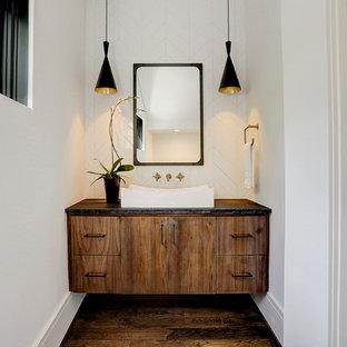 Cette photo montre un WC et toilettes tendance de taille moyenne avec un placard à porte plane, des portes de placard en bois brun, un WC séparé, un carrelage blanc, des carreaux de céramique, un mur blanc, un sol en bois brun, un plan vasque, un plan de toilette en granite, un sol marron et un plan de toilette noir.