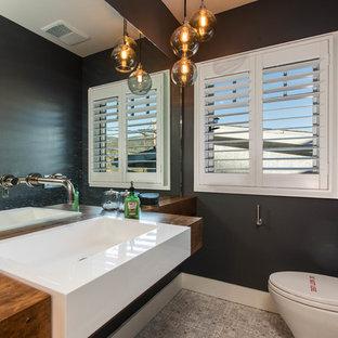 На фото: маленькие туалеты в стиле современная классика с открытыми фасадами, инсталляцией, черными стенами, полом из цементной плитки, накладной раковиной, столешницей из дерева, серым полом и коричневой столешницей