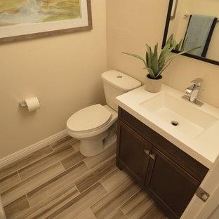 Mittelgroße Moderne Gästetoilette mit Schrankfronten im Shaker-Stil, dunklen Holzschränken, Wandtoilette mit Spülkasten, Vinylboden, integriertem Waschbecken und Mineralwerkstoff-Waschtisch in Los Angeles