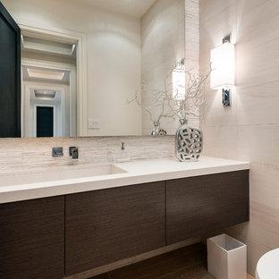 トロントの中くらいのコンテンポラリースタイルのおしゃれなトイレ・洗面所 (アンダーカウンター洗面器、フラットパネル扉のキャビネット、濃色木目調キャビネット、白いタイル、セラミックタイルの床、珪岩の洗面台、白い洗面カウンター) の写真