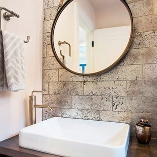 This is an example of a small traditional cloakroom in Minneapolis with flat-panel cabinets, medium wood cabinets, a one-piece toilet, brown tiles, travertine tiles, pink walls, slate flooring, a vessel sink, wooden worktops, black floors and brown worktops.
