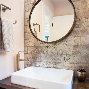 На фото: маленький туалет в стиле современная классика с плоскими фасадами, фасадами цвета дерева среднего тона, унитазом-моноблоком, коричневой плиткой, плиткой из травертина, розовыми стенами, полом из сланца, настольной раковиной, столешницей из дерева, черным полом и коричневой столешницей с