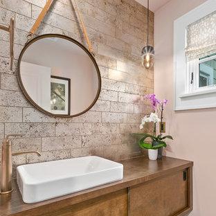 Ejemplo de aseo tradicional renovado, pequeño, con armarios con paneles lisos, puertas de armario de madera oscura, paredes rosas, suelo de pizarra, lavabo sobreencimera, encimera de madera, suelo negro y encimeras marrones