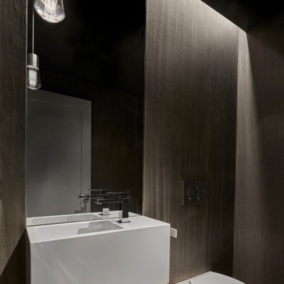 Small minimalist medium tone wood floor powder room photo in Chicago with a wall-mount toilet, gray walls, an integrated sink and white countertops