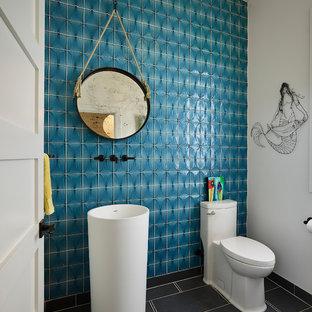 サンフランシスコの小さいビーチスタイルのおしゃれなトイレ・洗面所 (一体型トイレ、青いタイル、青い壁、ペデスタルシンク、グレーの床、白いキャビネット、ガラスタイル) の写真