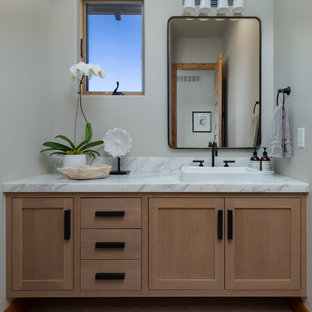 Example of a transitional gray floor powder room design in Denver with shaker cabinets, light wood cabinets, gray walls, a vessel sink, marble countertops and white countertops