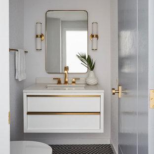 Moderne Gästetoilette mit flächenbündigen Schrankfronten, weißen Schränken, weißer Wandfarbe, Zementfliesen, Unterbauwaschbecken, schwarzem Boden und weißer Waschtischplatte in Chicago