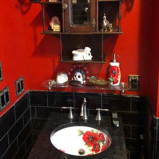 Cette photo montre un petit WC et toilettes éclectique avec un carrelage noir, un carrelage en pâte de verre, un mur rouge, un lavabo encastré, un plan de toilette en marbre et un plan de toilette noir.